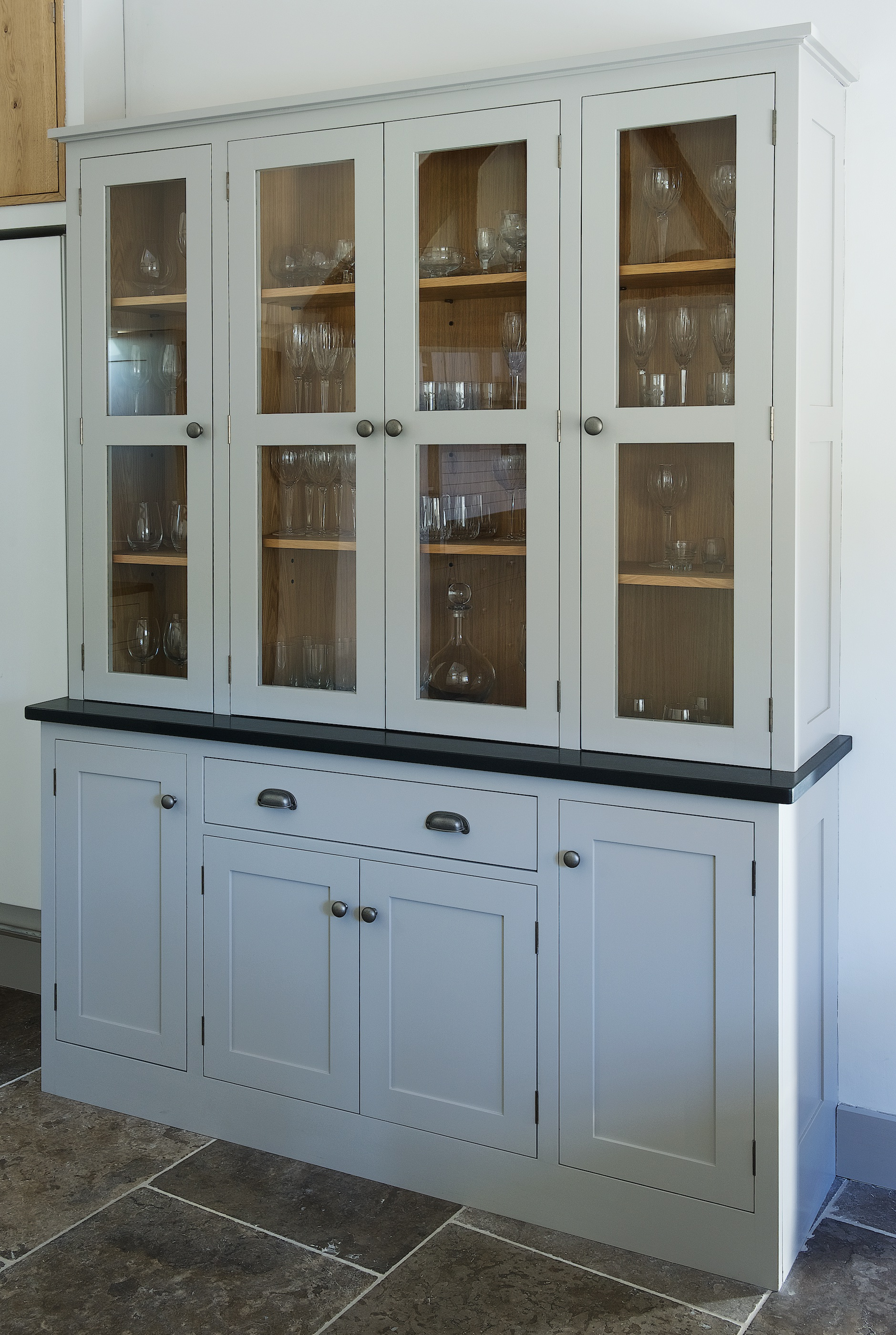 Grey bespoke french dresser with pewter hardware and glass display doors with solid oak shelving and closed cabinets below.
