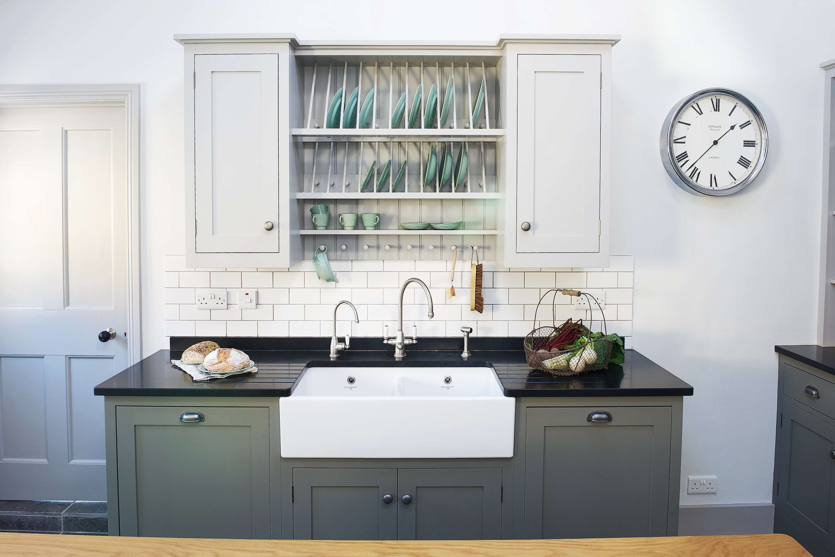 Grey and green shaker kitchen with pewter hardware and a double butler sink with black granite worktops and a plate rack wall cabinet.