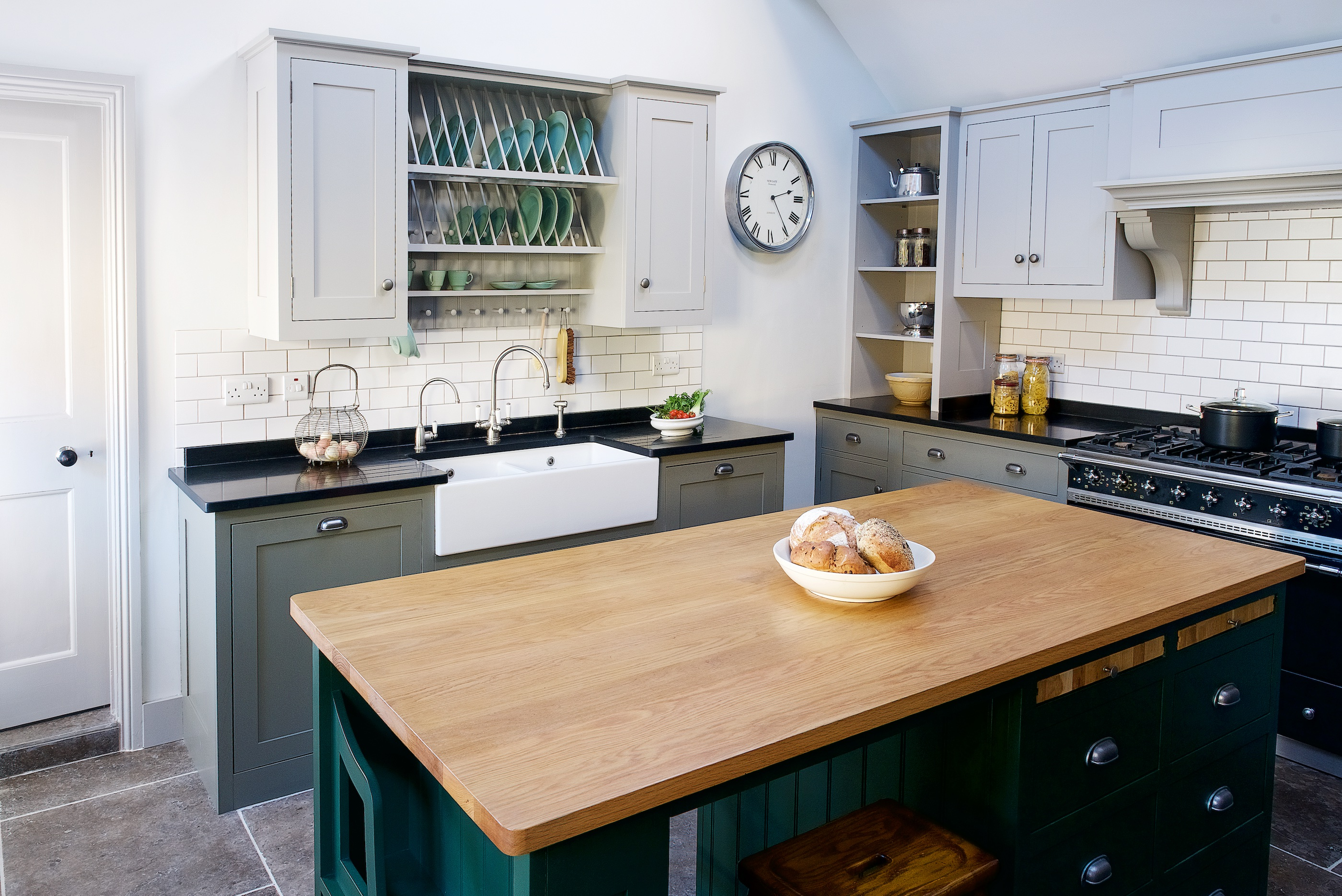 Bespoke shaker kitchen handpainted in Little Greene with a large island with oak worktop and white metro tile splashaback.