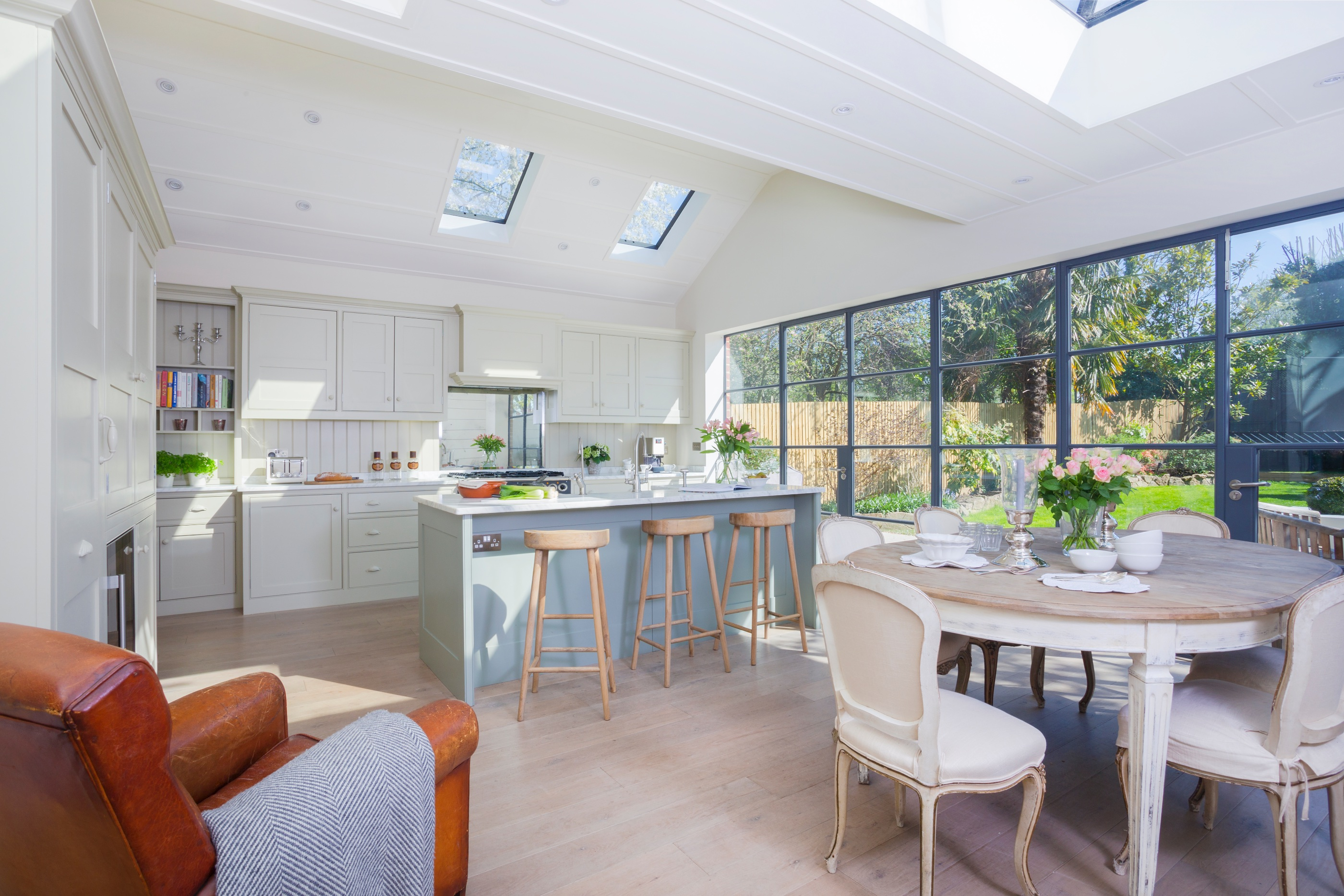 Open bespoke kitchen with island and open shelves with carrara worktops throughout and glass doors to garden.