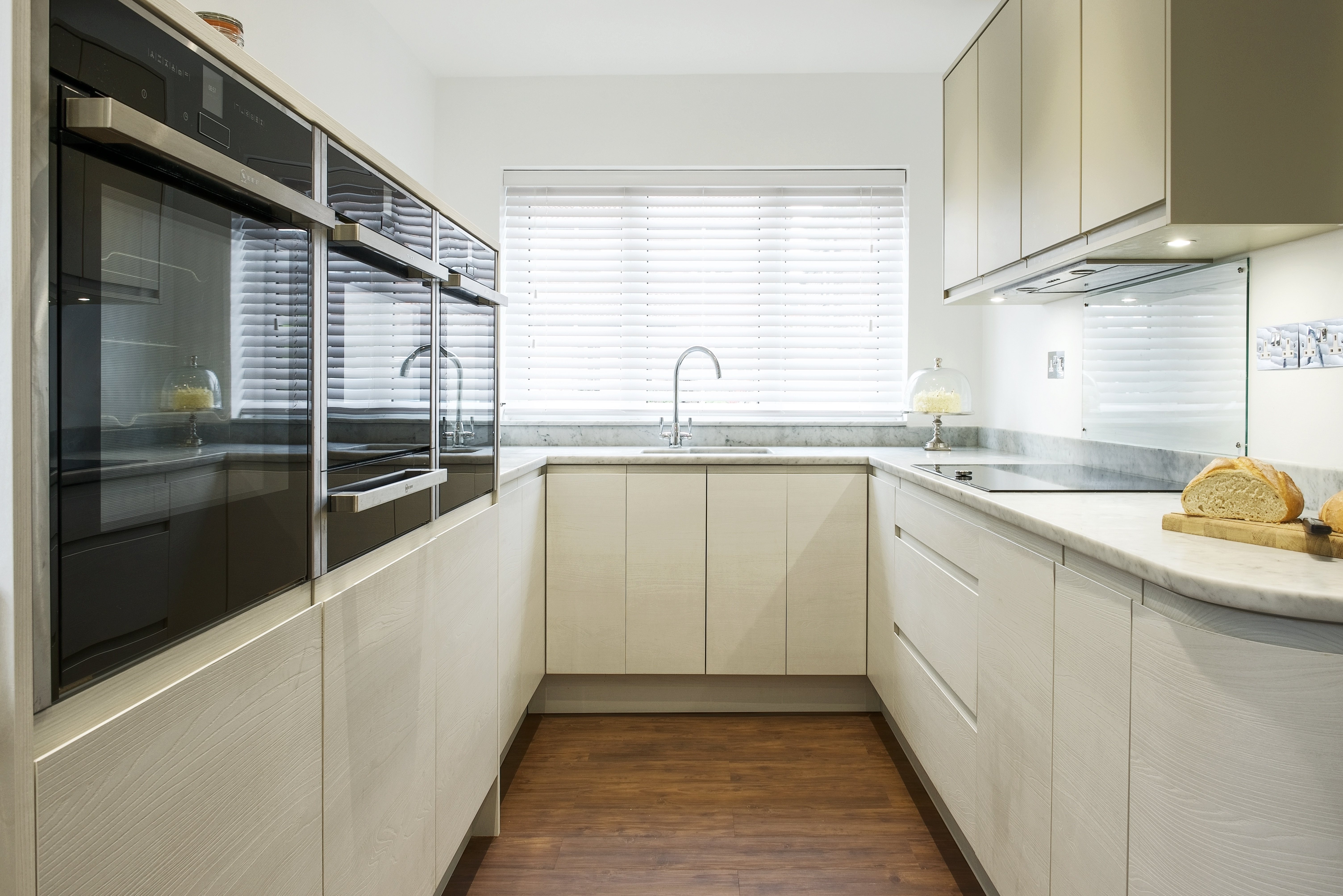White contemporary kitchen with Carrara marble worktops and Neff slide under ovens and microwave and Kholer sink and taps.