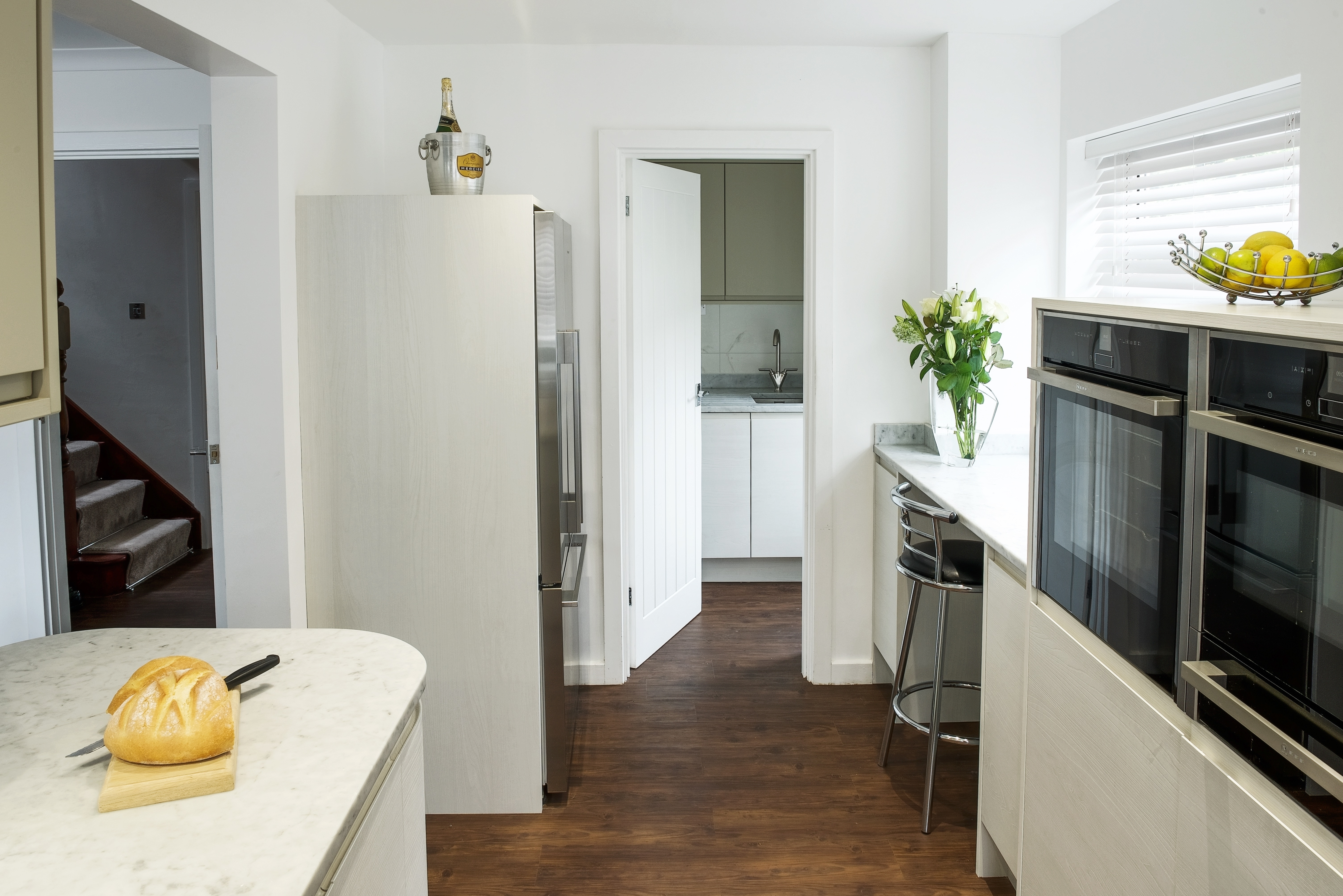 White contemporary kitchen with Neff slide under ovens and and a Fisher Paykel french door fridge freezer.