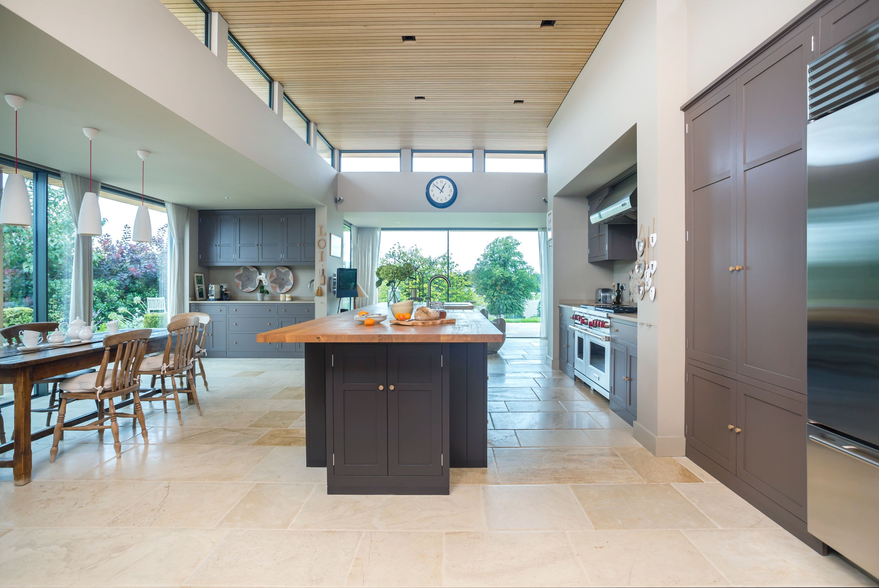 Open kitchen dining space with flagstone floor and a CK bespoke large island with a breakfast bar and built-in cabinets.