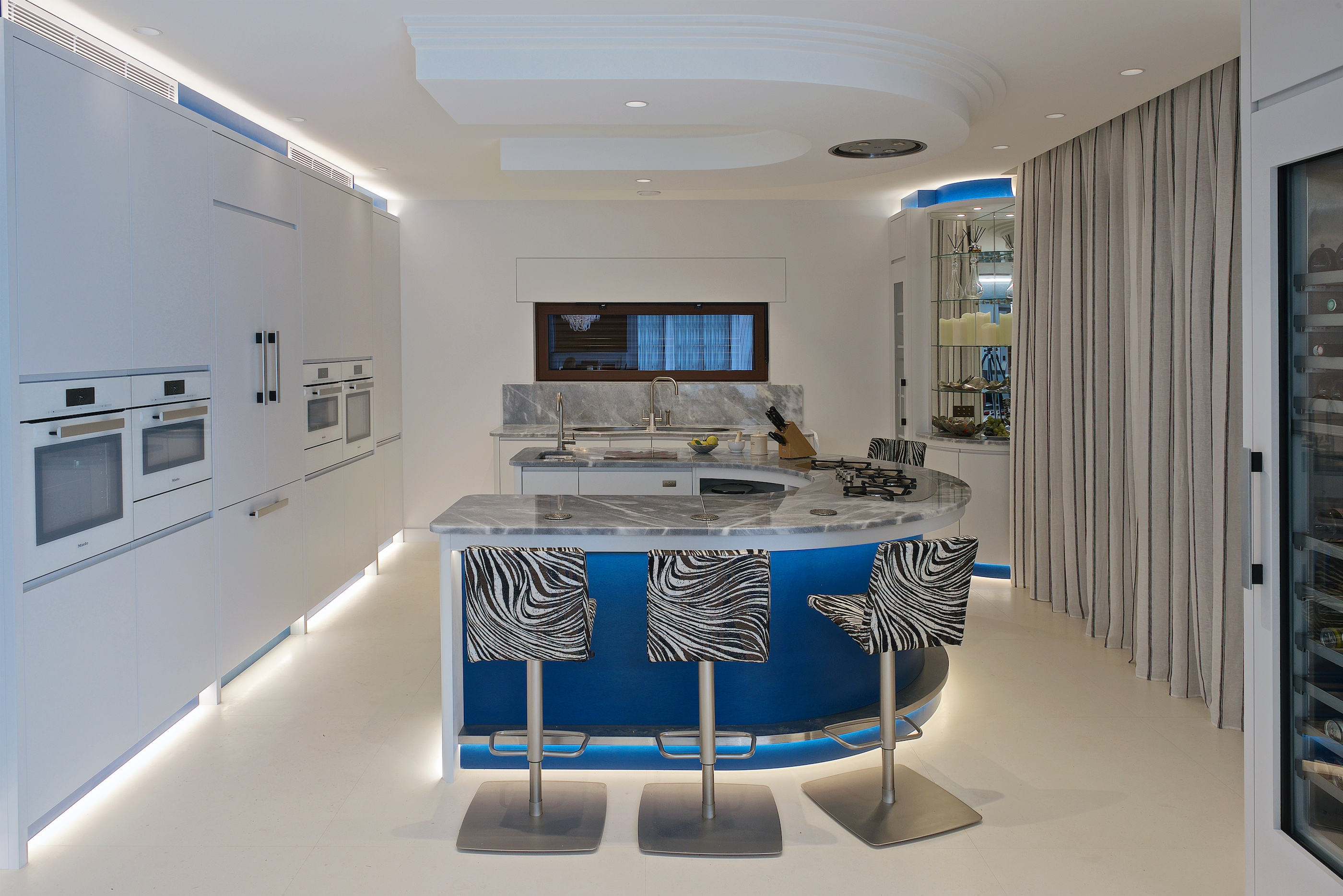 Contemporary blue curved kitchen island with Barazza Tao hob and zebra print kitchen stools with white kitchen cabinets and under cabinet lighting.