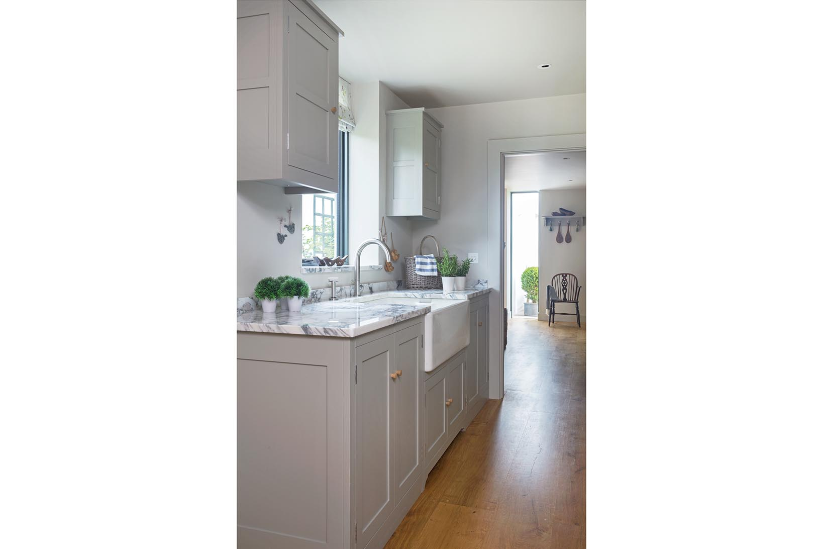 Plain shaker utility room in Farrow and Ball Harwick with polished Arrabascatta marble worktops and a reclaimed butler sink.