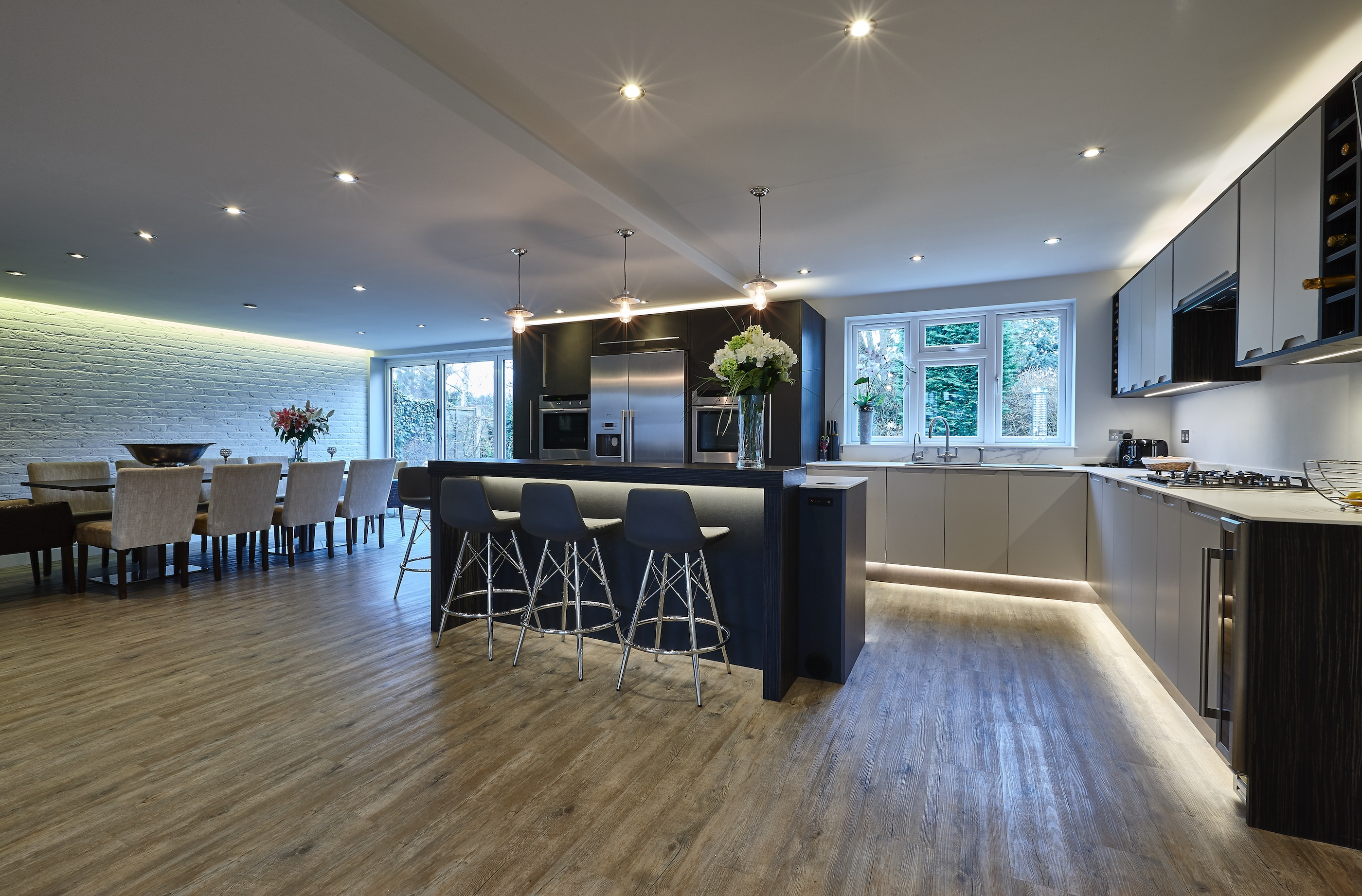 Bespoke contemporary CK kitchen with leather and grey cabinets and a large walnut wood island and stainless steel appliances.
