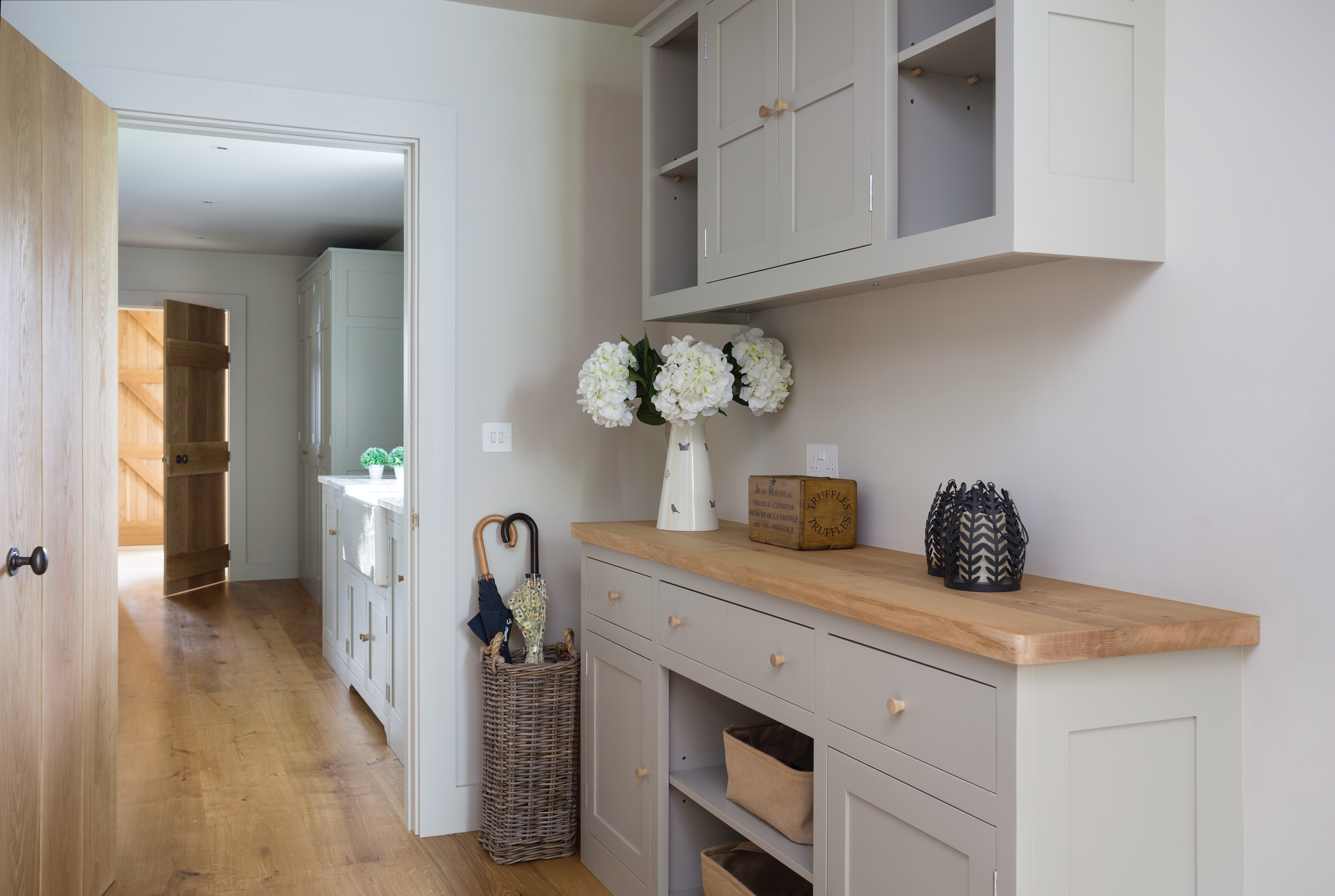 Bespoke shaker style boot room painted in Farrow & Ball Hardwick with oak worktops and handles leading into the utility room.