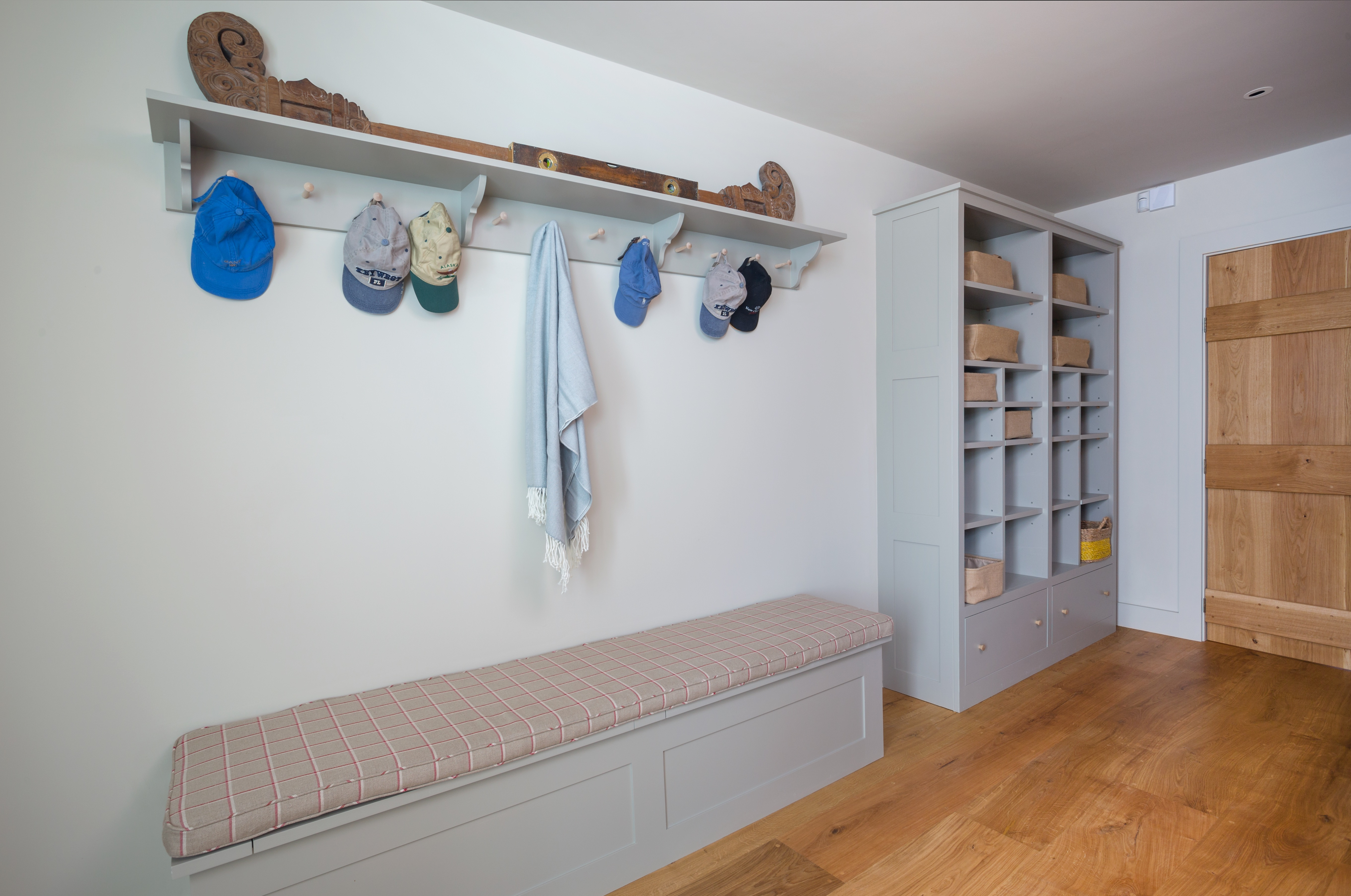 Bespoke shaker boot room storage shelves with oak handles and bench with peg rack all painted in Farrow & Ball Hardwick.