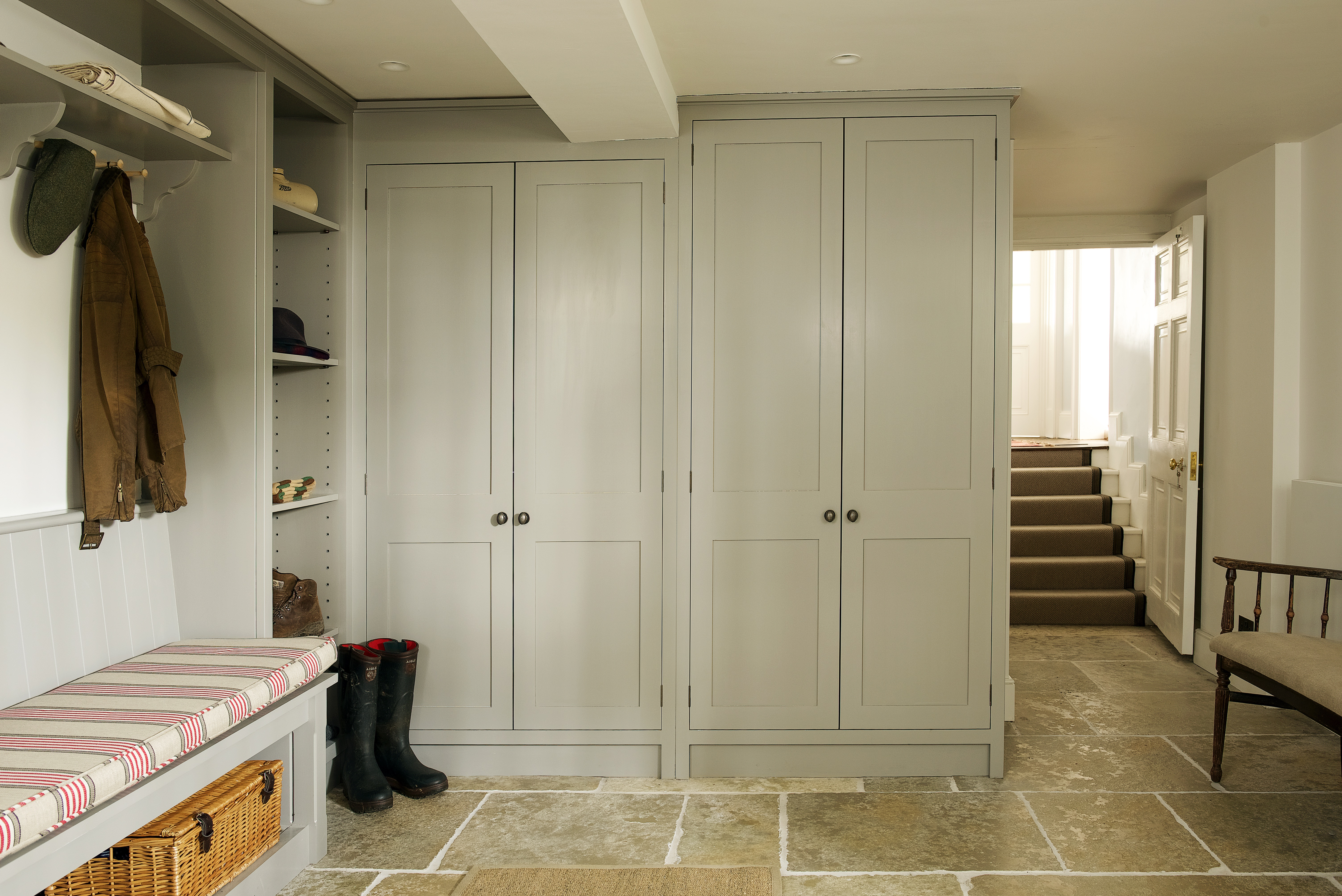 Bespoke handmade boot room with open shelves and shaker pegs on a bracketed shelf and a bench all hand painted in grey.