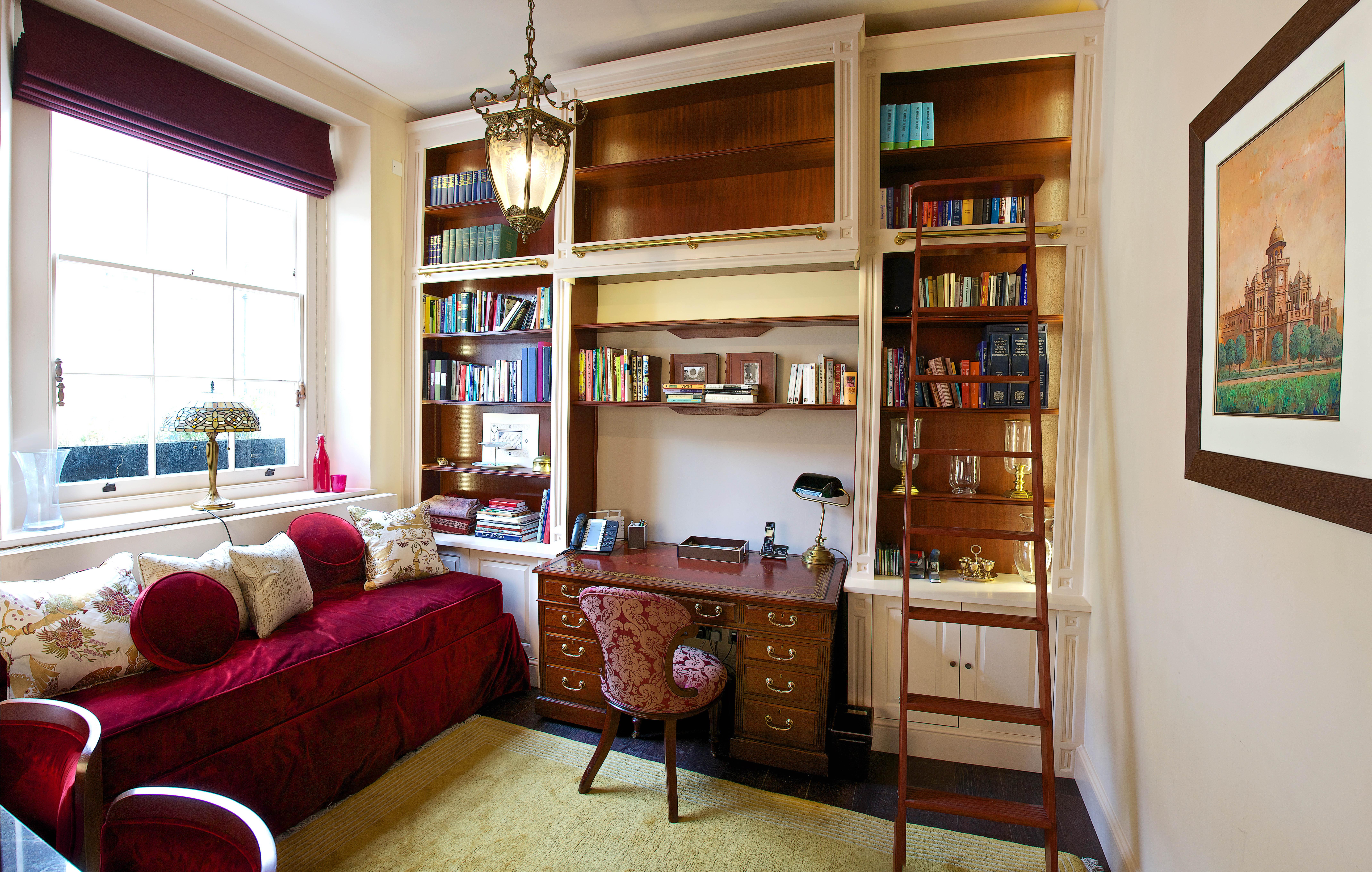 Charlie Kingham bespoke handmade study with built in shelves and sliding ladder on brass rail.
