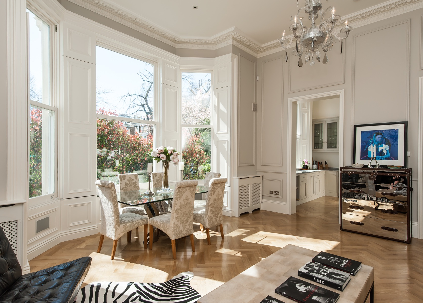 High ceiling dining living room with bay windows and wall panelling looking into the bespoke CK shaker grey kitchen