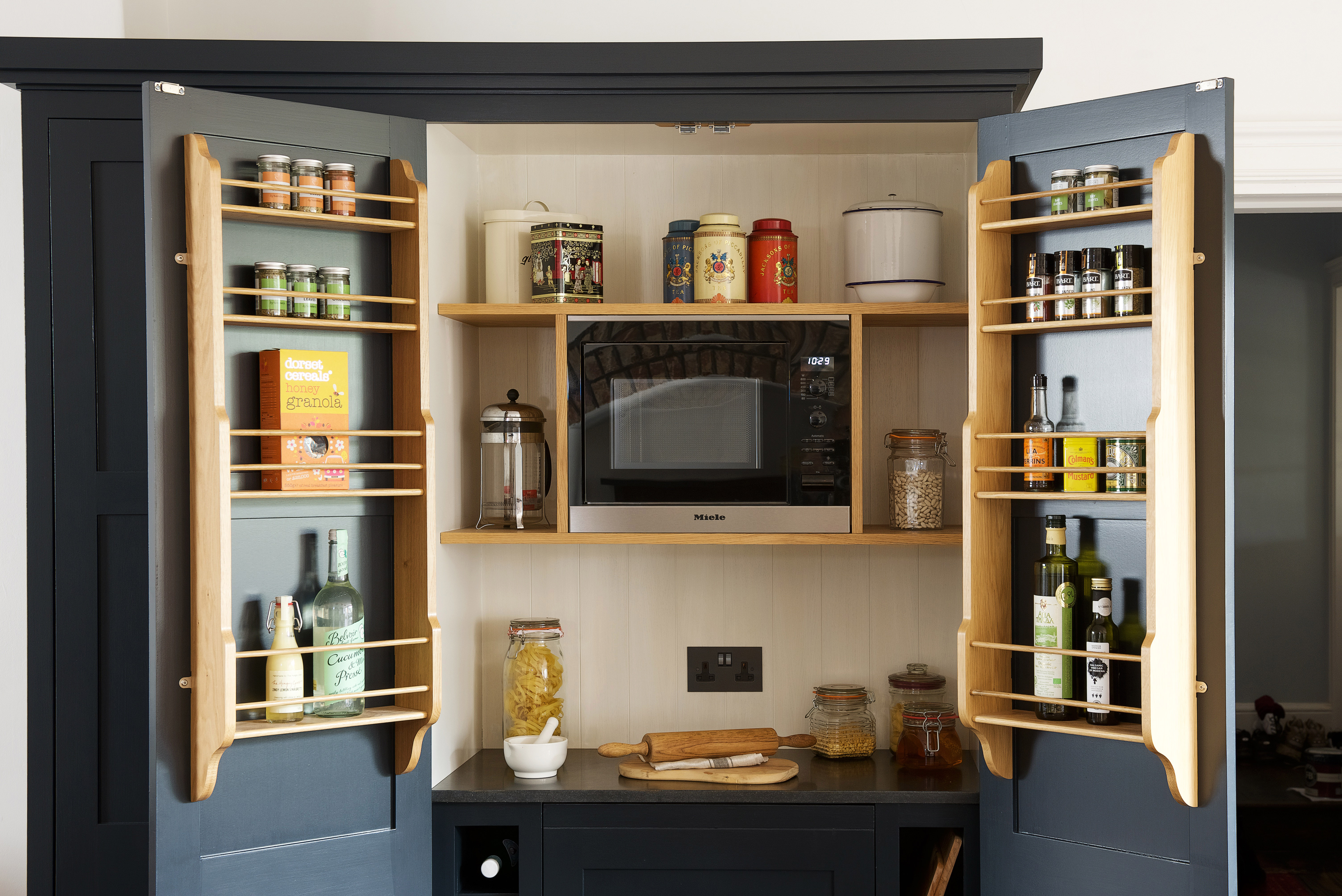 Bespoke handmade shaker larder hand painted in Farrow & Ball Railings with spice racks and built in microwave and cooler.