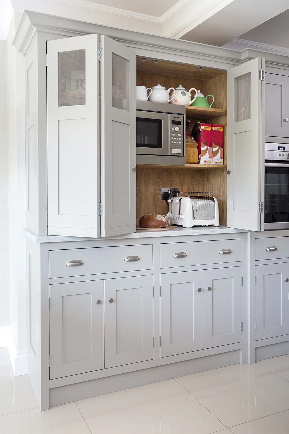 Grey breakfast pantry with bi fold doors and stainless steel hinges and handles with a Neff microwave.
