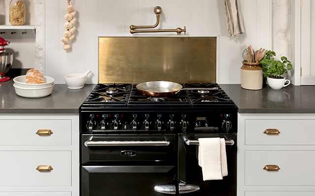 White shaker kitchen with wall shelves and brass hardware with a black AGA range cooker with brass splash back and pot filler.