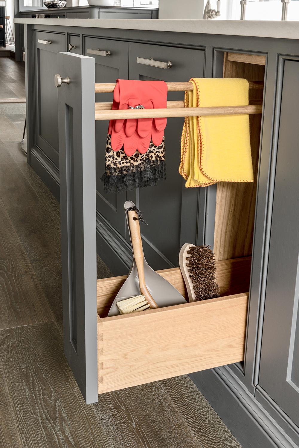 Grey kitchen island with an open pull out dovetailed cupboard for cleaning equipment made of solid oak with three rails for hanging cloths.