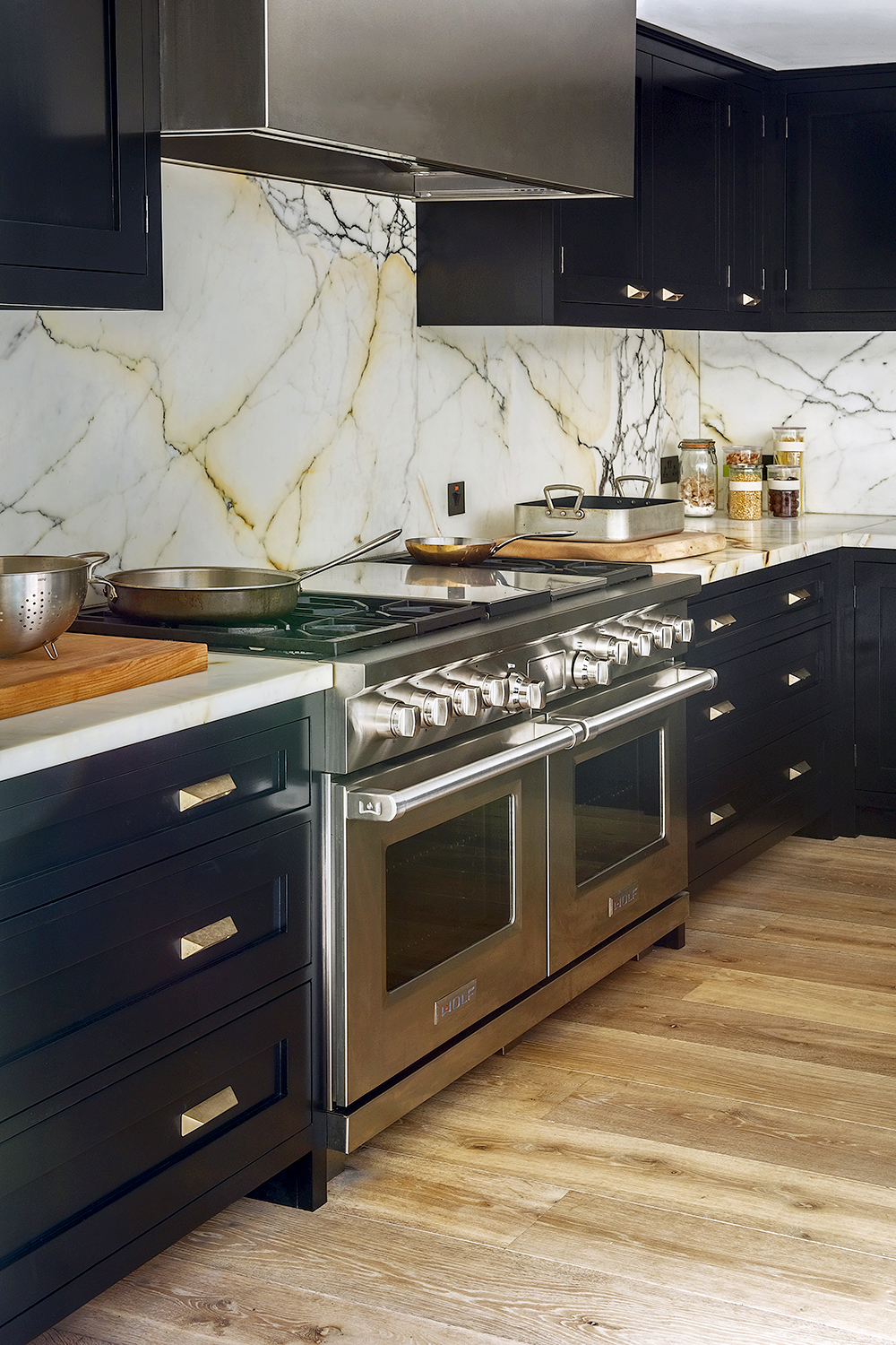 Wolf range cooker built in to marble veined worktops and splash backs with cabinets in MyLands Sinner with Westin Hood extractor and aged brass hardware.