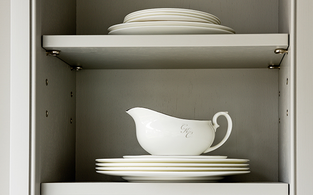 Bespoke Charlie kingham tableware displayed in a georgian classic kitchen with open shelves painted grey.