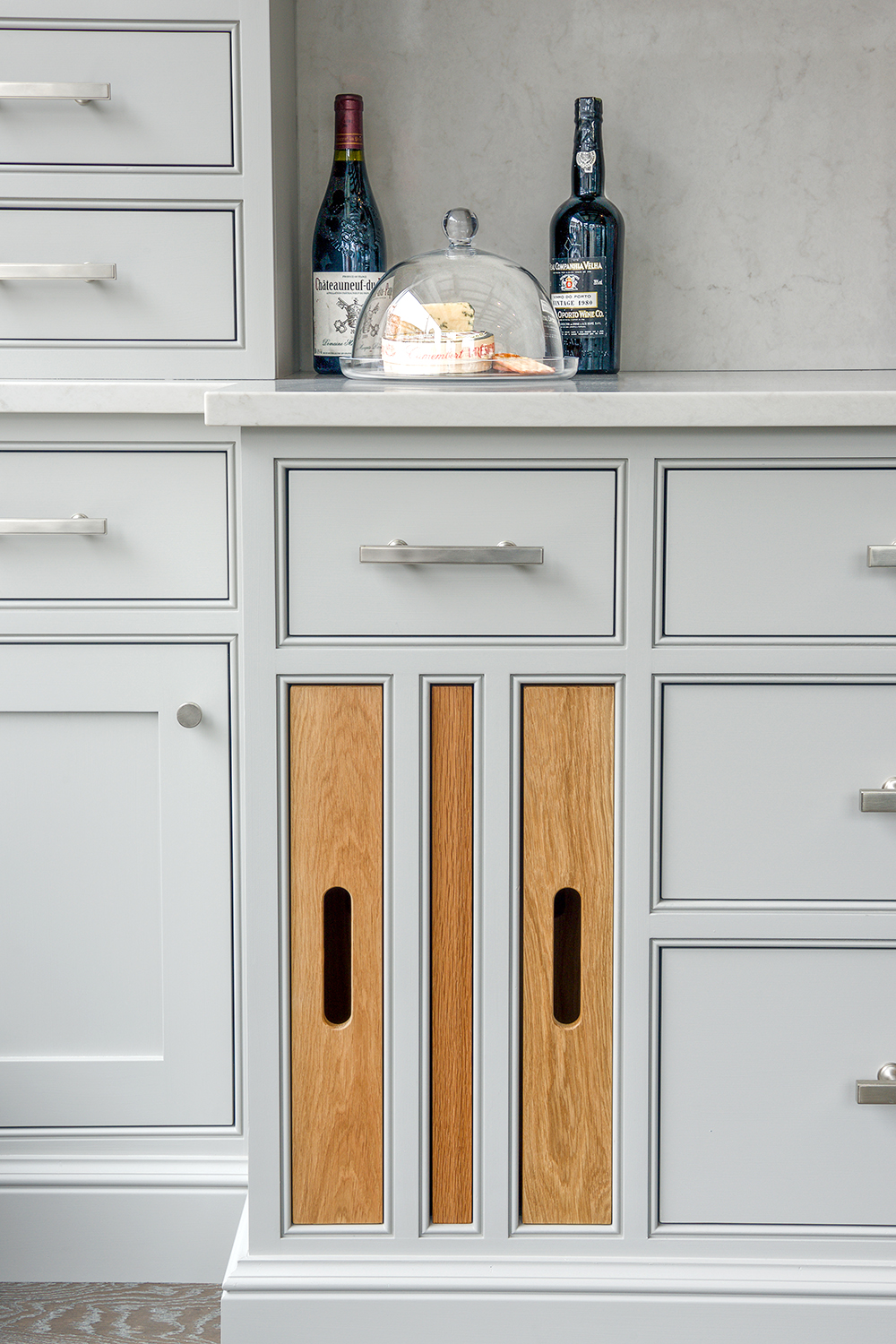 Bespoke kitchen painted in light grey with Caesarstone London Grey worktop and stainless steel handles and solid oak pull out trays built in with one pulled out.