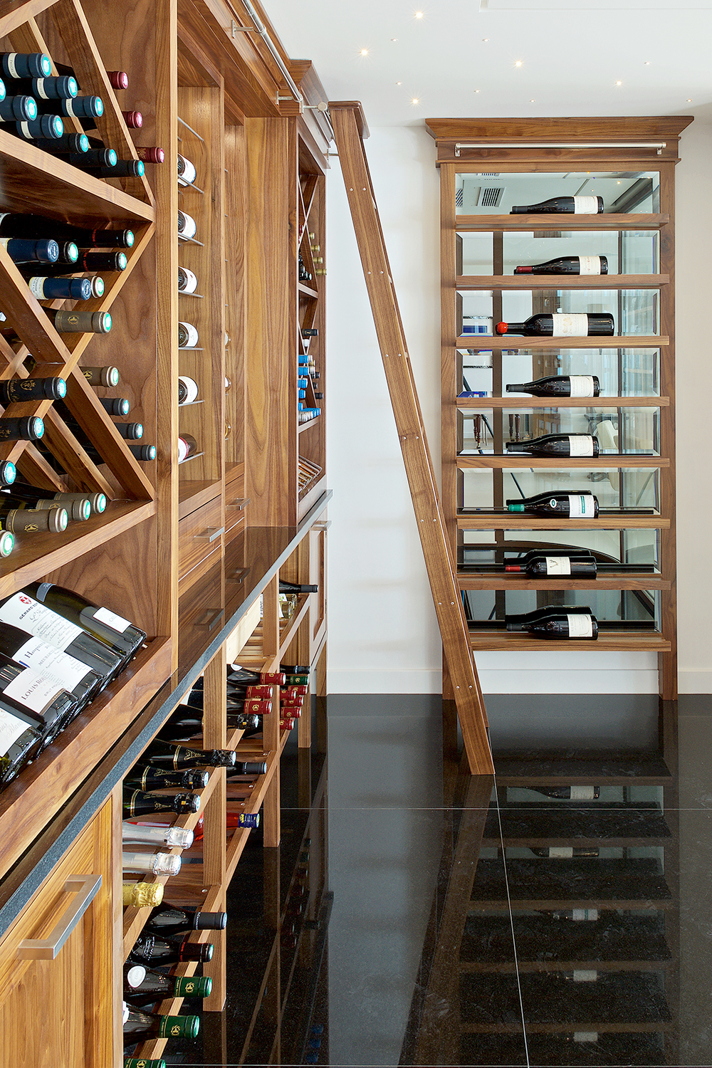 Bespoke wine room with shelving and racks made from solid American oak with sliding ladder on rail and Caesarstone Piatra Grey worktops.