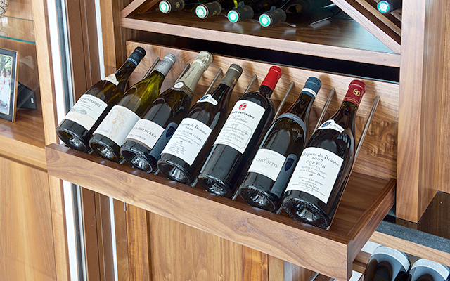 Detail of wine shelf with stainless steel bars on solid American oak shelves in bespoke wine room.
