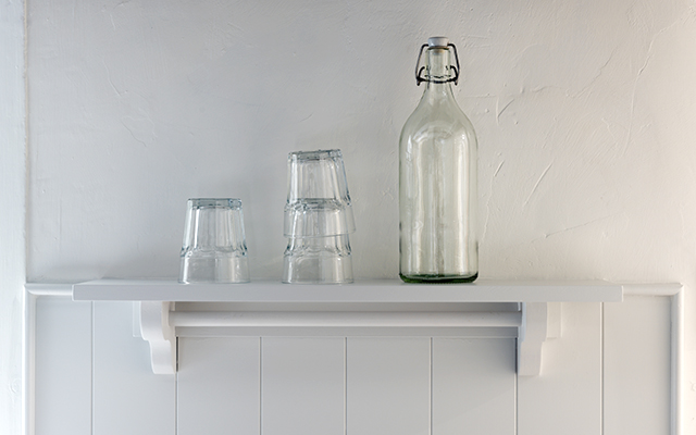 Bespoke small wall shelf hand-painted white with a rail beneath and glasses and glass water bottle on display.