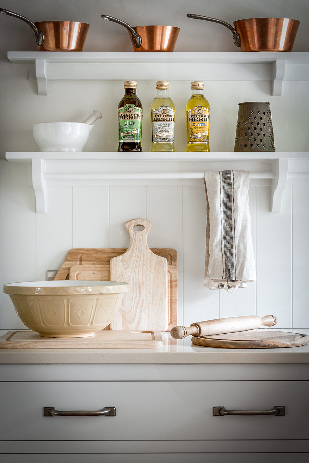 Classic shaker Kingham kitchen drawers and shelves with country copper pots and baking equipment.