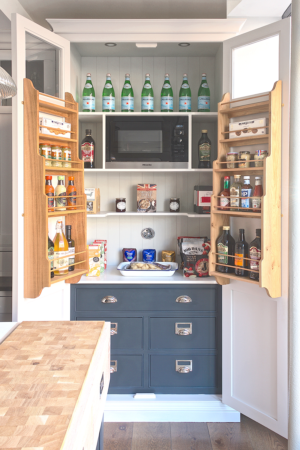 Open larder with white frame and doors and solid oak door racks with bottom drawers painted in MyLands Bond Street and Miele microwave.