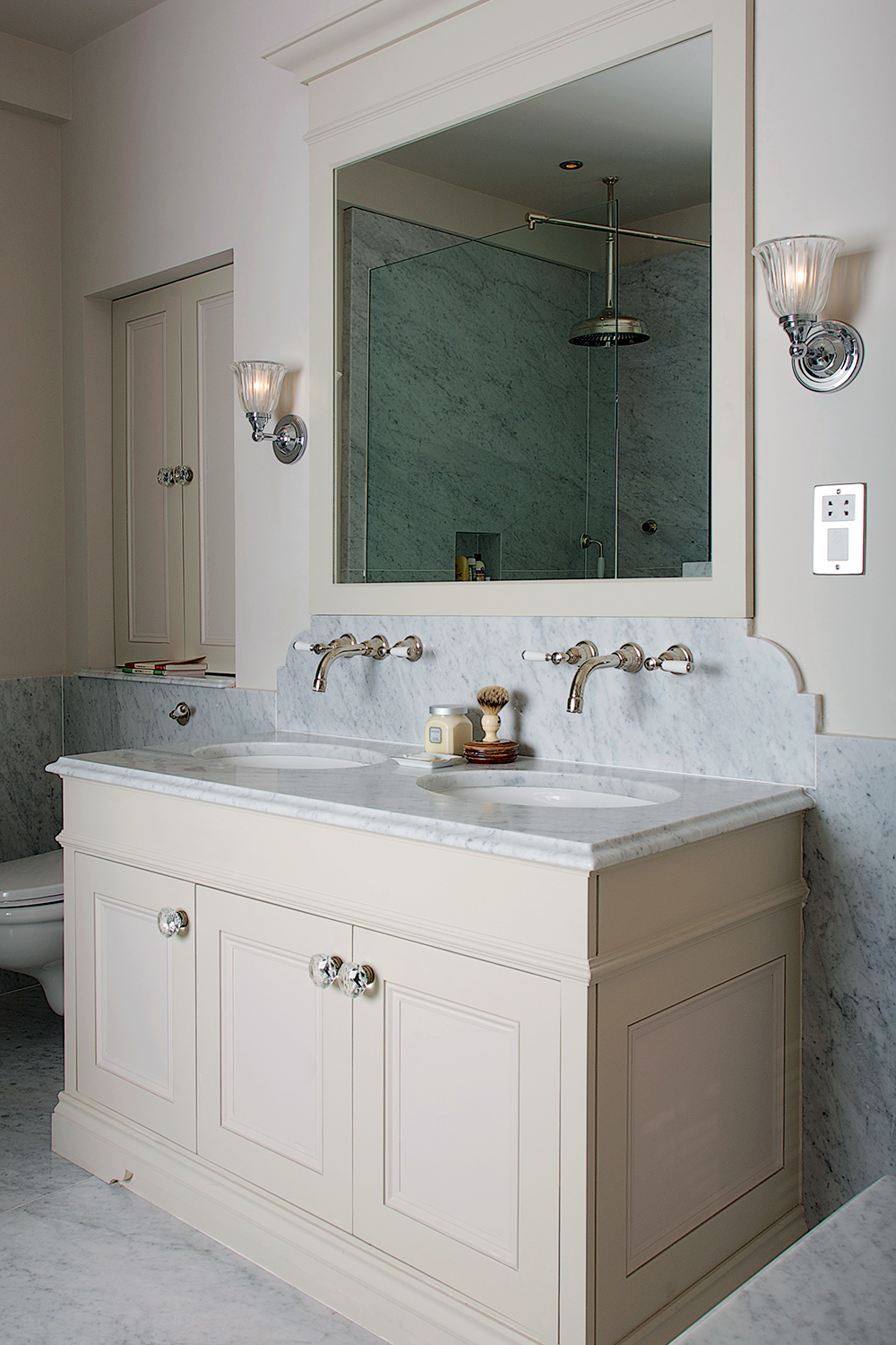 Bespoke Charlie Kingham bathroom double sink unit in cream with marble worktops and wall mounted taps in chrome.