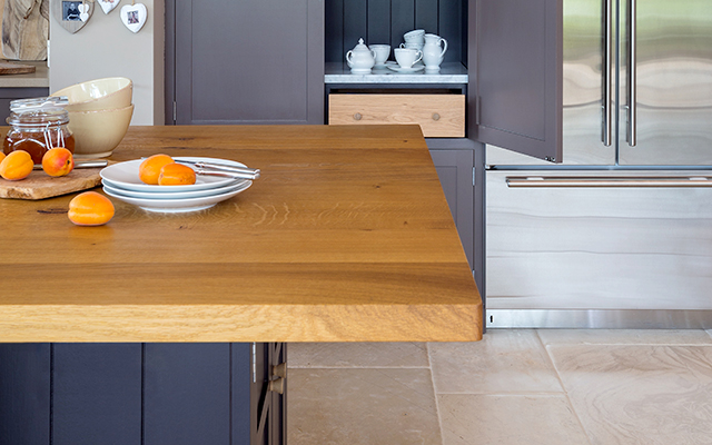 Island oak worktop close up with open tea and toast cabinet painted in Clay next to Subzero double fridge in stainless steel.