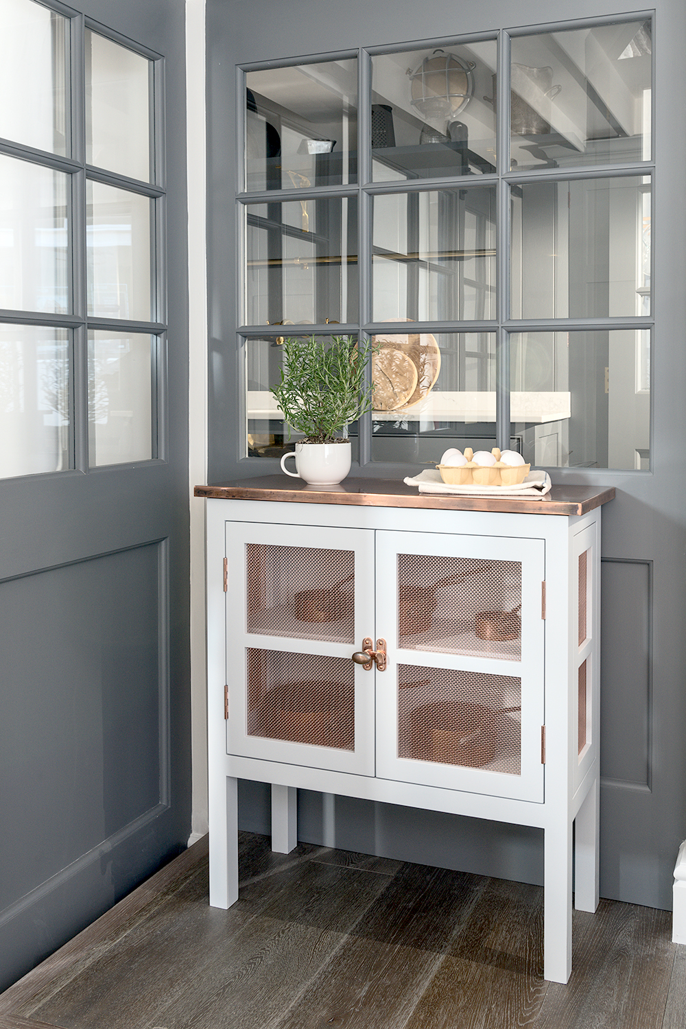Dairy cabinet with copper mesh panels and copper handles with frames painted light grey and an ageing copper worktop.