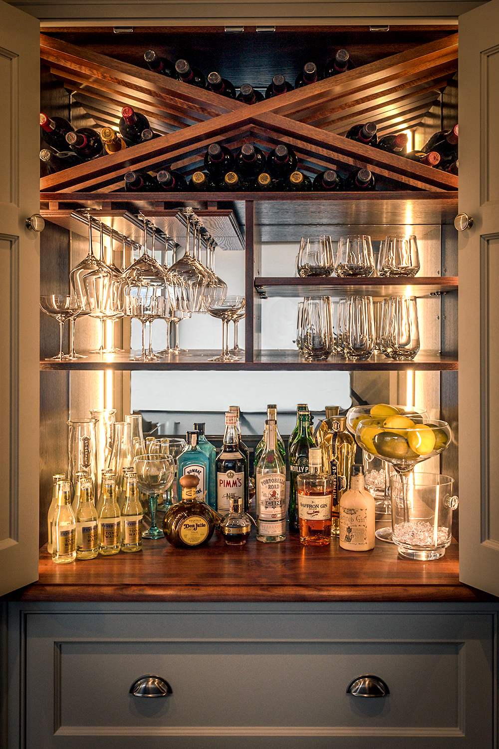 Open drinks cabinet with cherry wood interior and worktop and handprinted pavilion grey doors and drawer fronts with chrome cup handles with lights on.