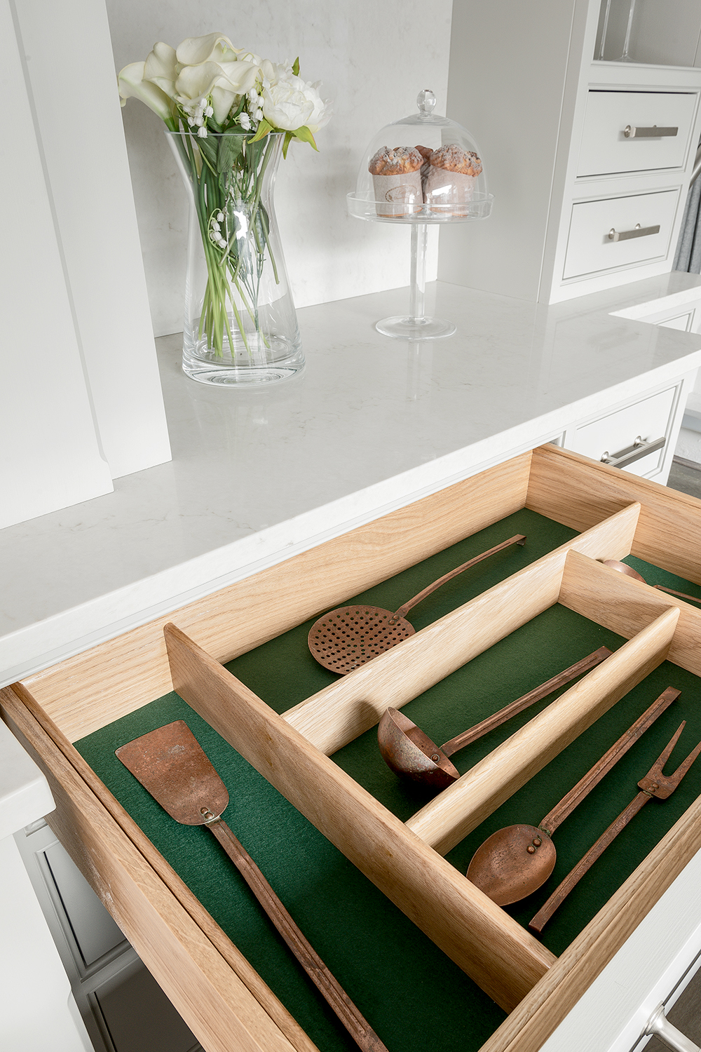 Open grey cutlery drawer in solid oak with green lining and vintage utensils on display with Caesarstone London Grey worktop and cabinets painted grey and stainless steel handle.