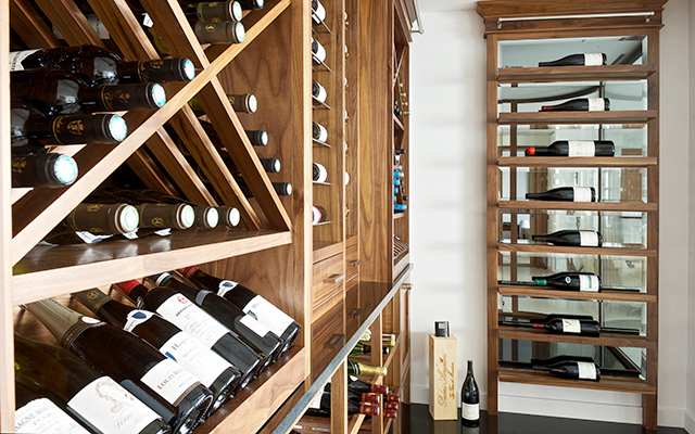 Bespoke wine room with shelving and racks made from solid American oak with Caesarstone Piatra Grey worktops and mirror backs.