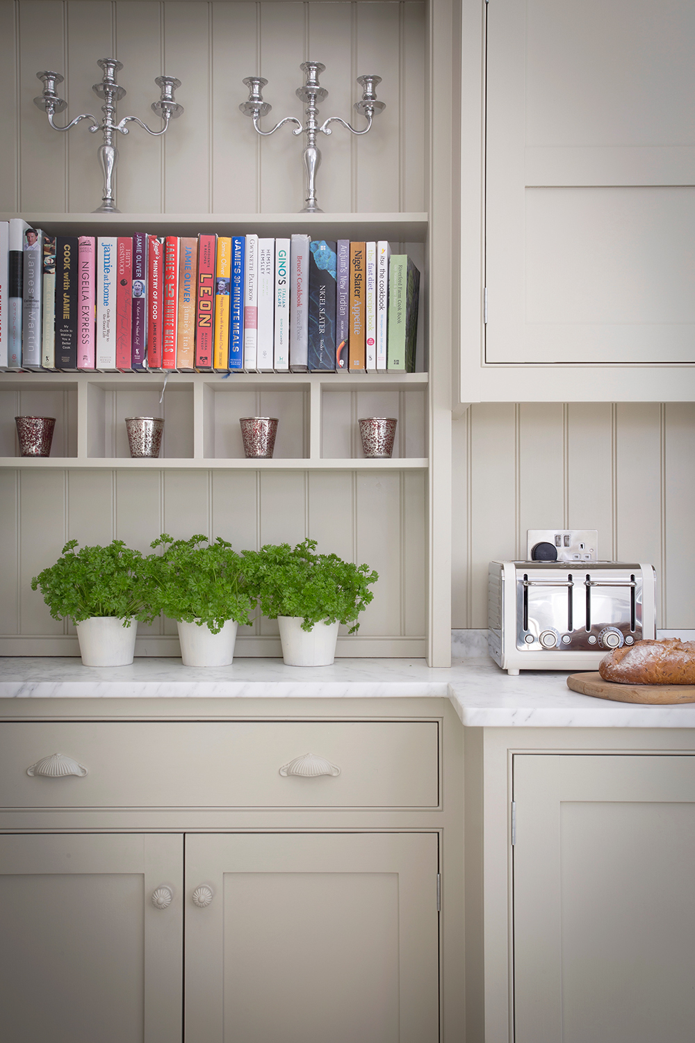 Open shelves with recipe books in Georgian classic kitchen and herbs above carrara marble worktops with a cream toaster.