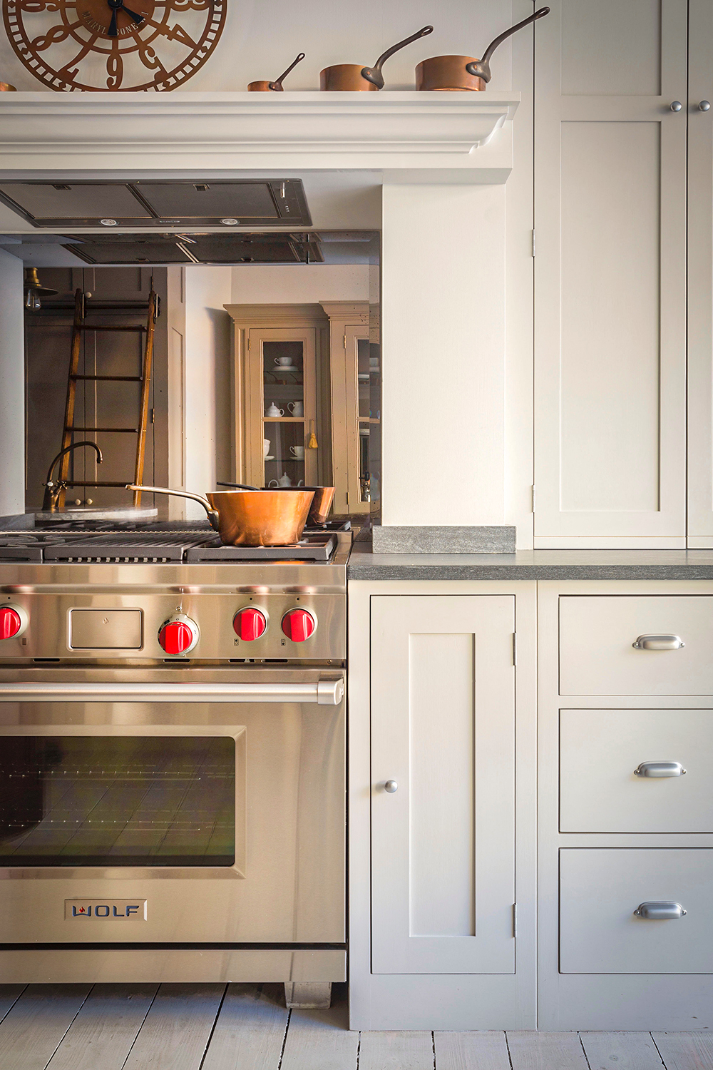 Wolf oven with red knobs and copper pot on the hob in a white georgian classic kitchen with canopy above the cooker.