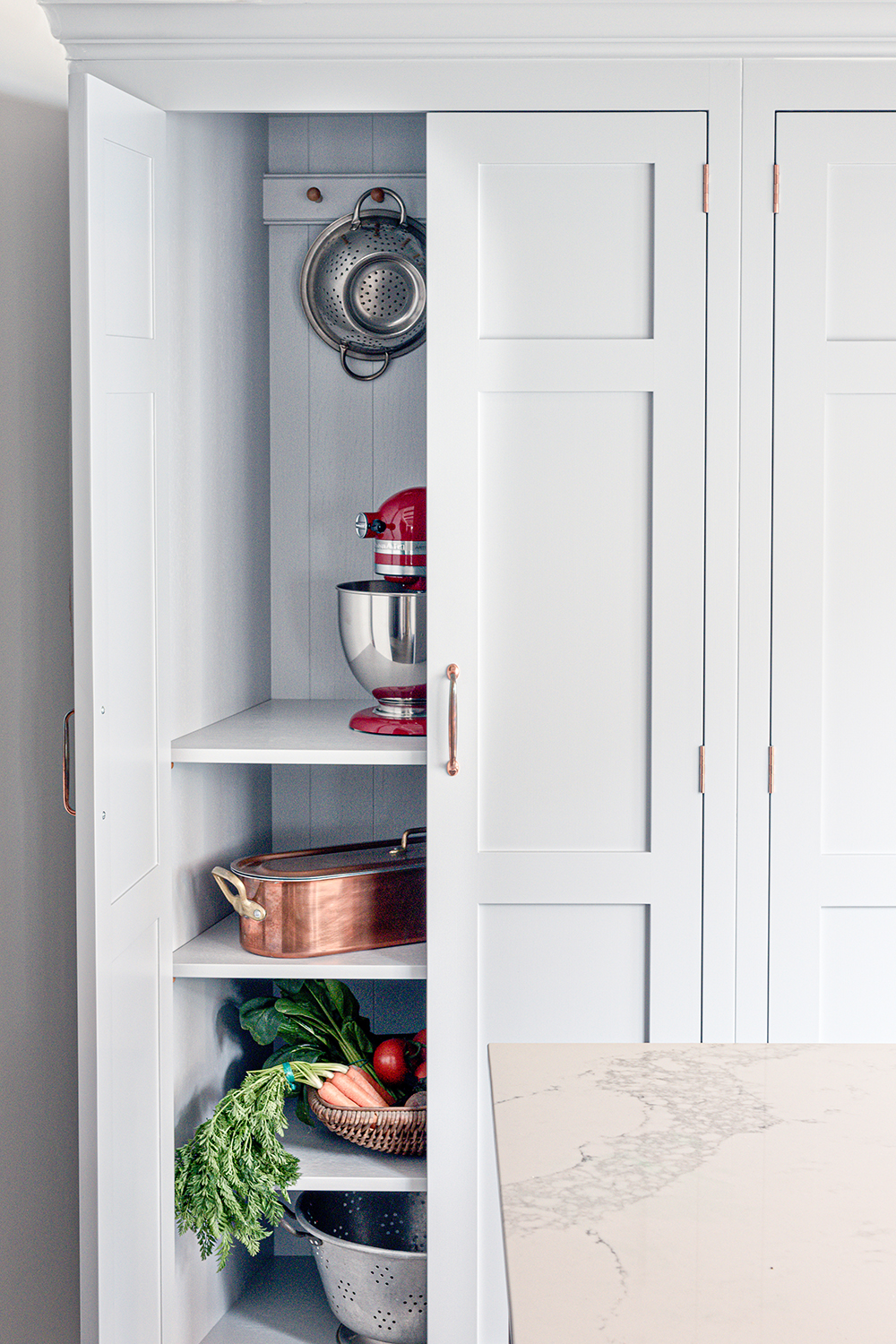 Half open larder cabinets with adjustable shelves and shaker pegs hand painted in light grey with a red Kitchen Aid mixer.