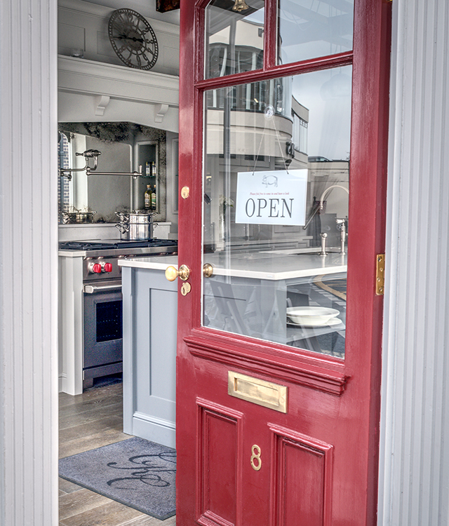 Front door of Charlie Kingham Guildford showroom ajar with open sign on display.