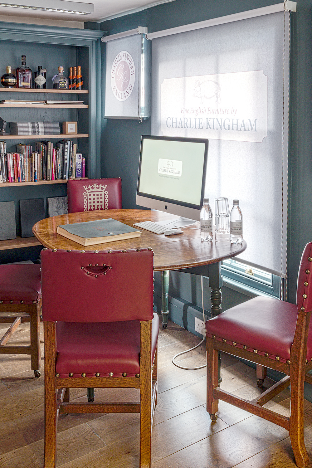 Charlie Kingham Guildford showroom design room with red leather chairs and a Mac with shelving and books.