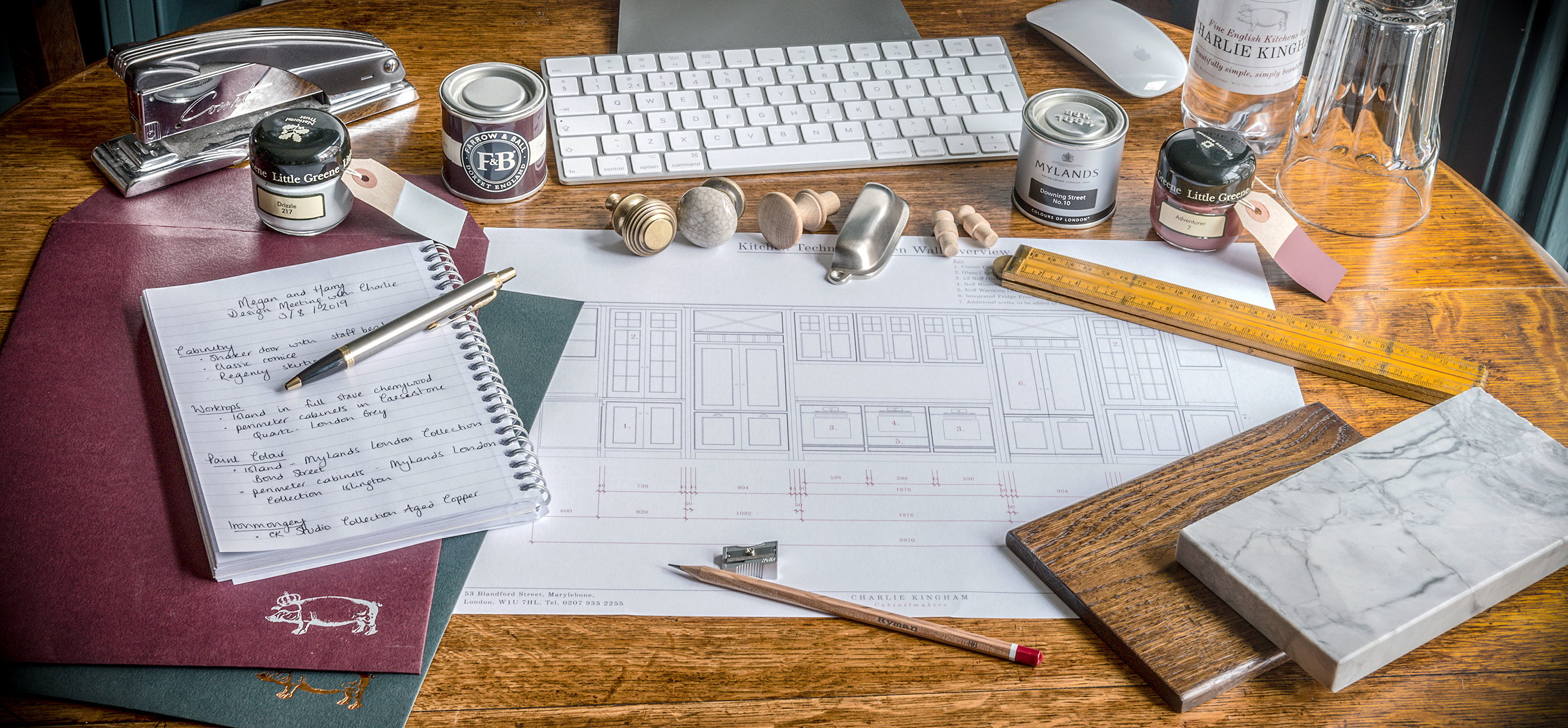 Charlie Kingham design room table flat lay with plans, samples and design notes.