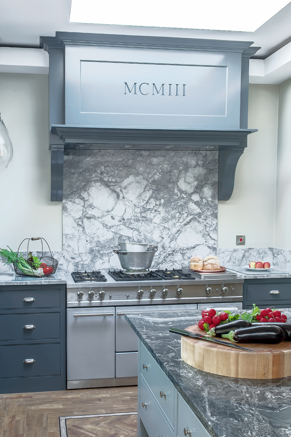 Bespoke canopy above large range cooker with marble worktops and splashback in a classic shaker kingham kitchen painted dark grey with chrome accents.