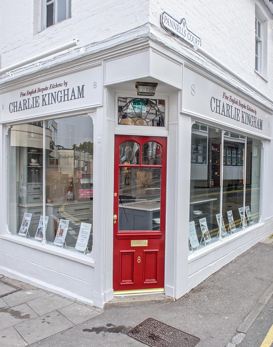 Charlie Kingham bespoke kitchens Guildford showroom red front door with road sign.