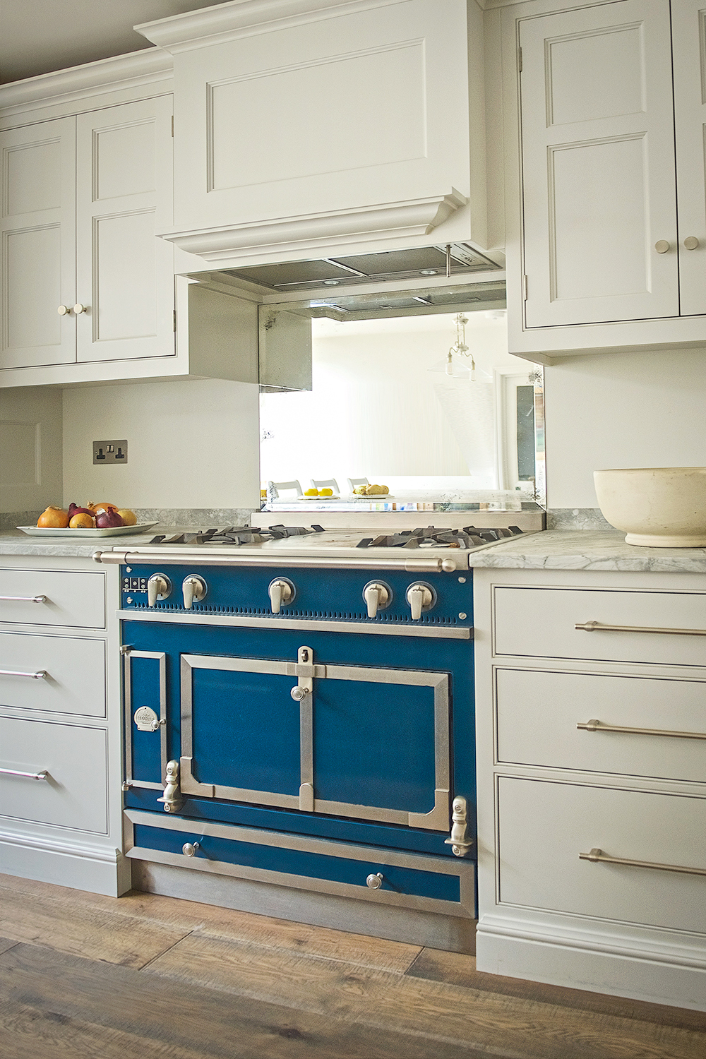 La Cornue range cooker in blue with antique mirror splash back and shaker cabinets with classic cornice with brushed chrome handles.
