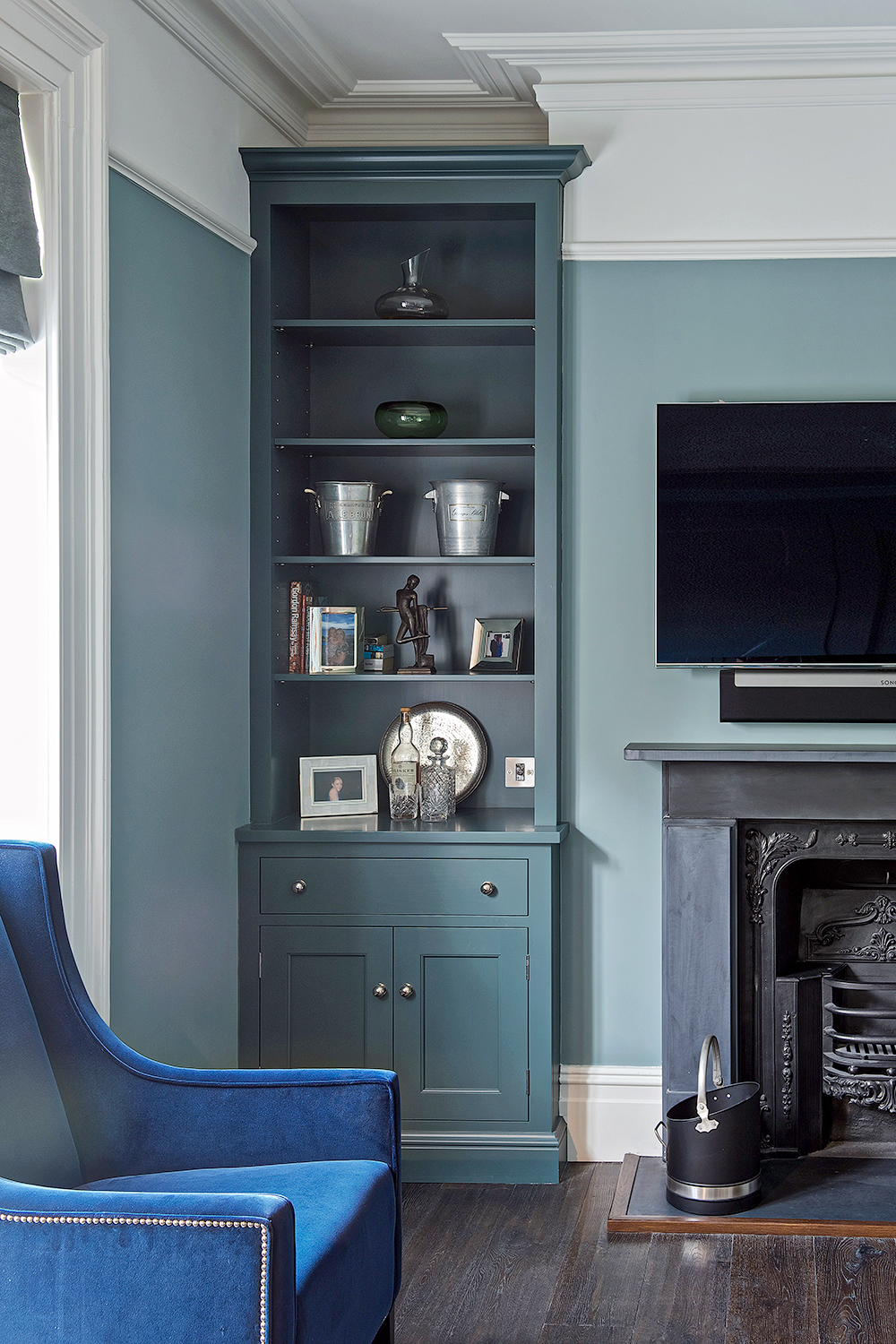 Built in alcove cabinet with drawers and cupboards and open shelves painted blue with chrome handles next to fireplace.