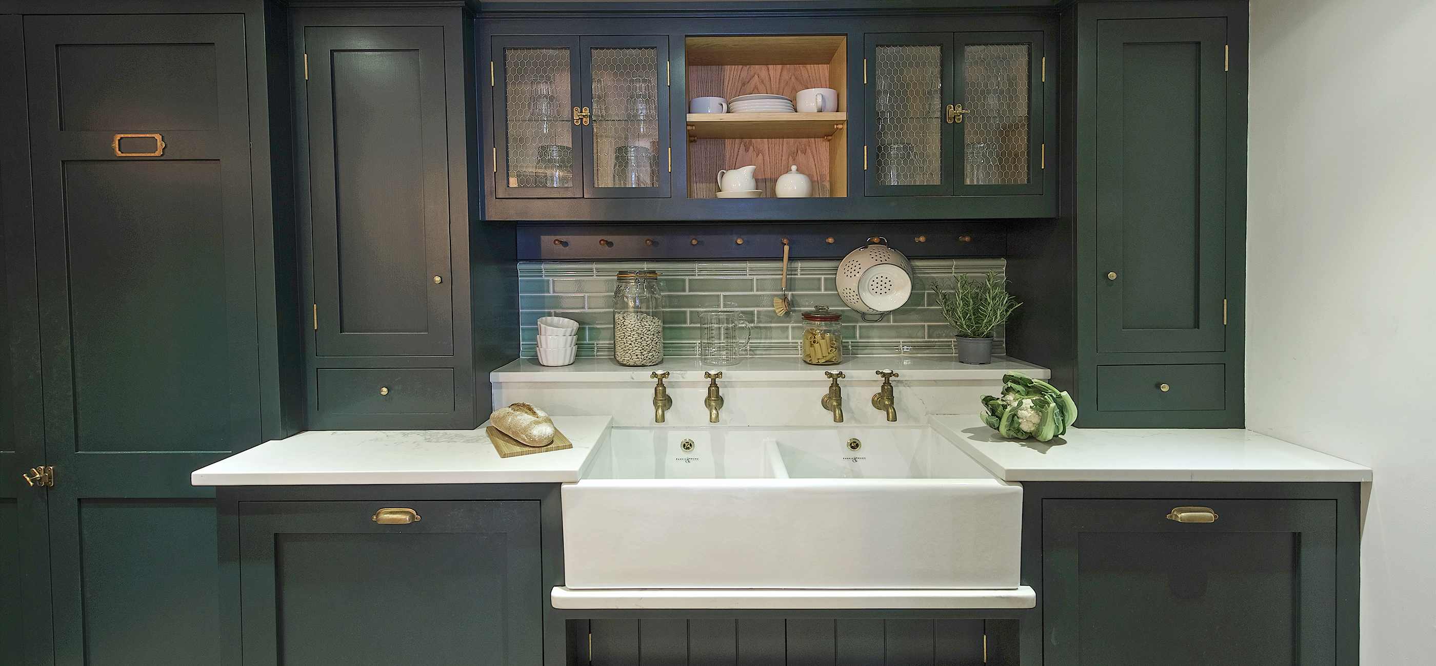 Shaker kitchen units with mesh front cabinets above and a large double sink with brass taps and green metro tile backsplash with white marble worktop.