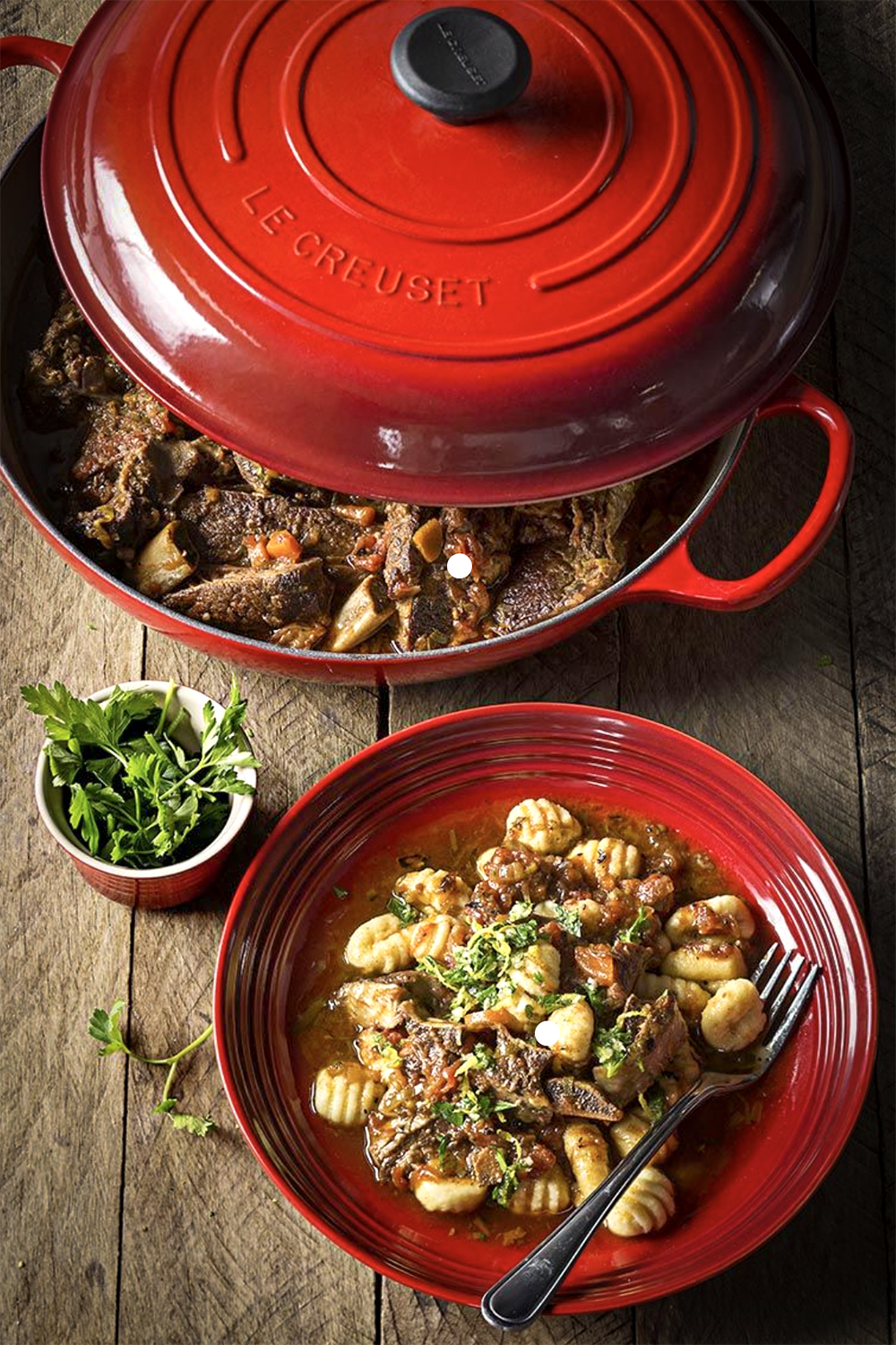Red Le Creuset ramekin, plate and casserole dish with lid half off showing beef bourgignon and gnocchi.