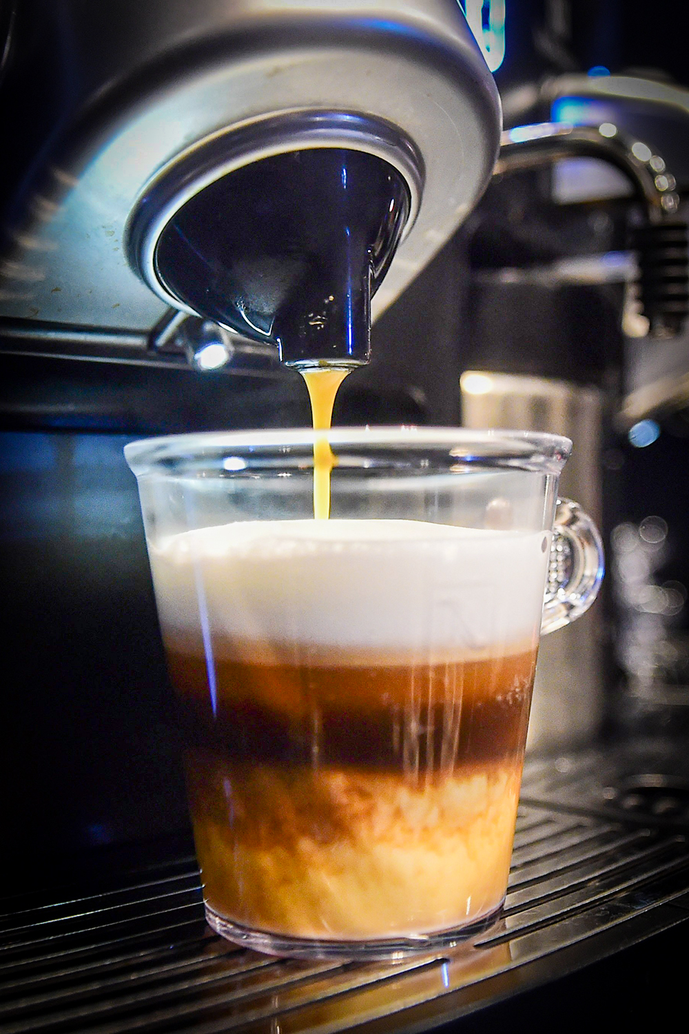 A triple-layered espresso pouring into a clear mug from Nespresso Gemini CS200 pro coffee machine
